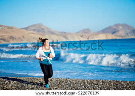 Young fitness plus size woman in earphones jogging on the beach. Sport concept. Healthy lifestyle.