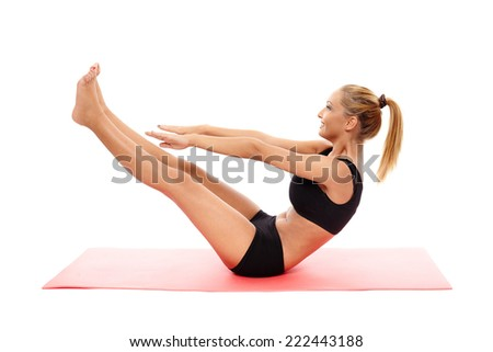 Young fitness woman doing abs crunches on a mat isolated on white - stock photo