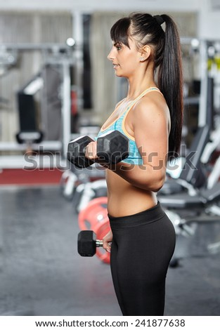 Young fitness woman doing biceps workout with dumbbells, in a gym - stock photo