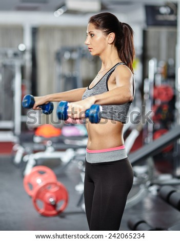 Young fitness woman doing deltoids workout with dumbbells in a gym - stock photo