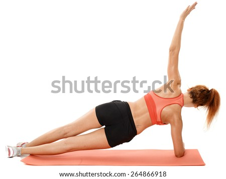 Young fitness woman doing exercises on a mat isolated on white