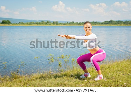 Young fitness woman doing squats in nature by the lake. Cute blonde Caucasian teenage girl in pink and white sportswear working out outdoors in summer. Natural light, mild retouch.