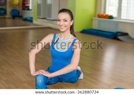 Young fitness woman doing stretching at the gym. Sports training in the fitness studio at the beautiful girl.