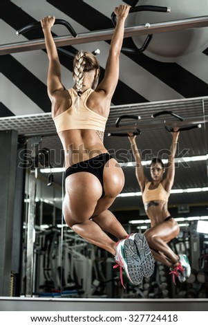 young fitness woman execute exercise on prelum abdominale, on horizontal bar in gym, vertical photo - stock photo
