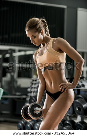young fitness woman execute exercise with dumbbells in gym, vertical photo - stock photo