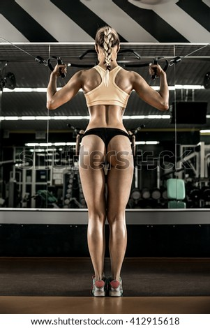 young fitness woman execute exercise with exercise-machine Cable Crossover in gym, vertical photo - stock photo