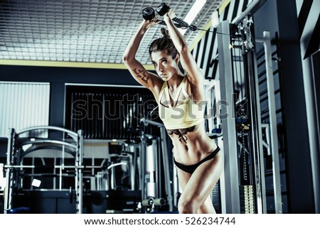 young fitness woman execute exercise with exercise-machine on triceps in gym, horizontal photo