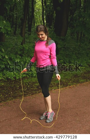 Young fitness woman exercising - jumping with skipping rope in the park