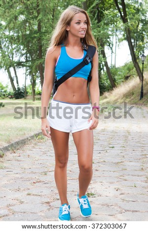 Young fitness woman holding a mat and going to join yoga class in the park