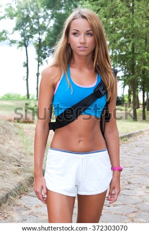 Young fitness woman holding a mat and going to join yoga class in the park - stock photo