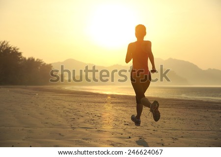 young fitness woman jogging at sunrise beach