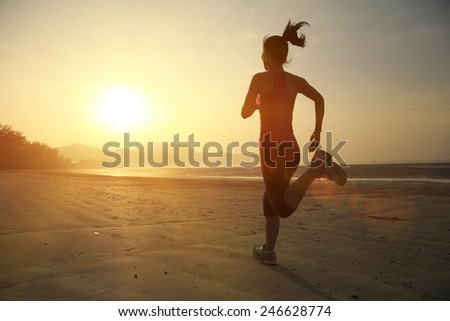 young fitness woman jogging at sunrise beach  - stock photo
