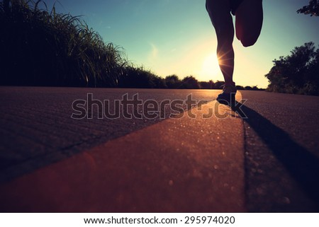 young fitness woman legs running on sunrise seaside trail - stock photo