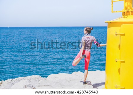 Young fitness woman making stretching next yellow beacon - Handsome girl have break after jogging looking horizon sea view  - Wellness lifestyle concept - Vintage saturated filter - stock photo