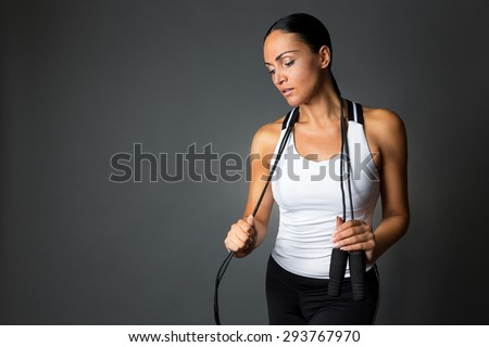 Young fitness woman posing with jump rope against dark grey background. - stock photo
