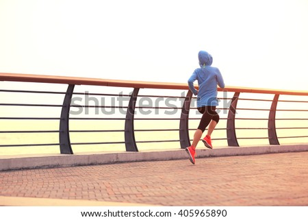 young fitness woman runner athlete running at seaside road - stock photo