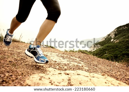 young fitness woman runner legs running on seaside mountain trail