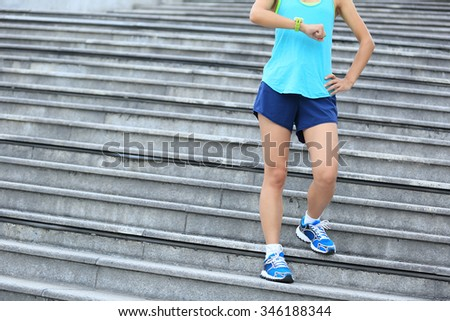 young fitness woman runner looking at her sports watch