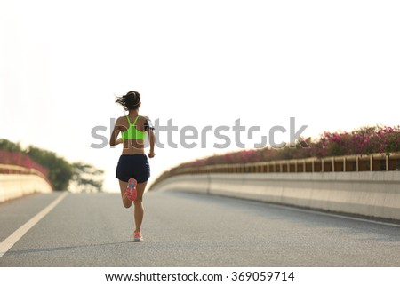 young fitness woman runner running at city road - stock photo