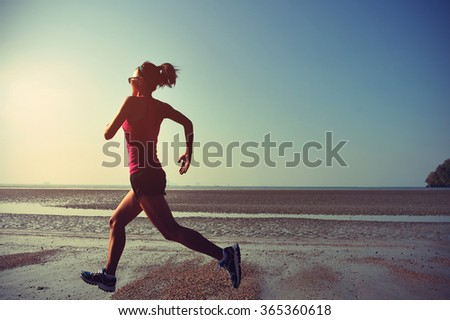 young fitness woman runner running at sunrise beach - stock photo