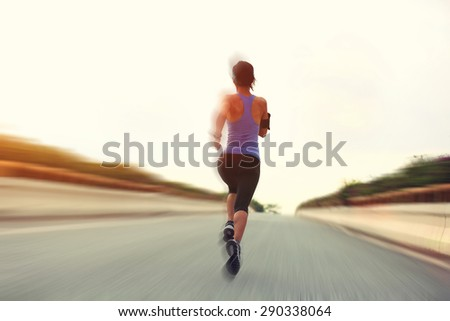 young fitness woman runner running on city road - stock photo