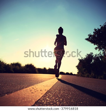 young fitness woman runner running on sunrise seaside road - stock photo