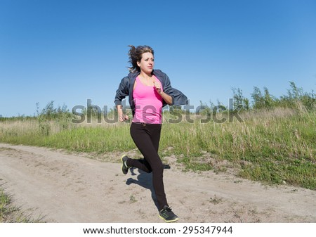 young fitness woman running at country  trail