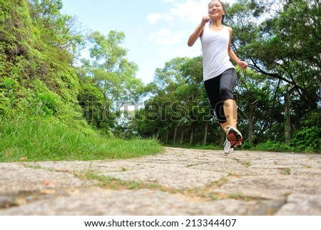 young fitness woman running at forest stone trail