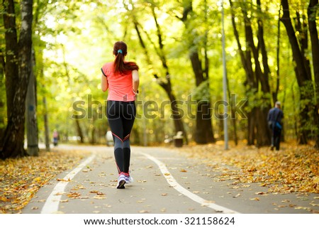 young fitness woman running at forest trail in park