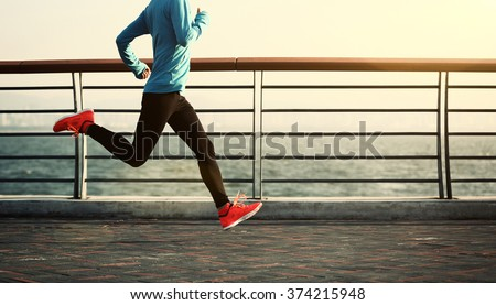 young fitness woman running at seaside - stock photo