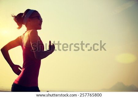 young fitness woman running at sunrise beach  - stock photo