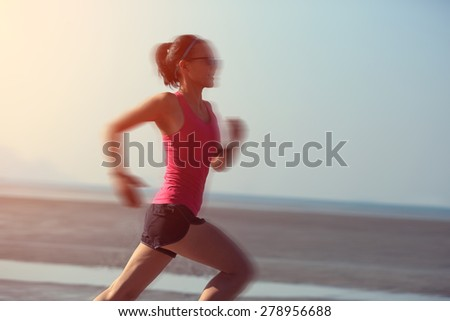 young fitness woman running at sunrise beach