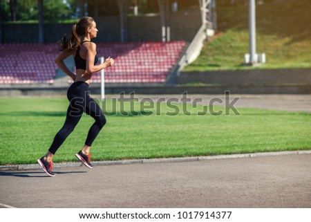 Young fitness woman running on a stadium track. Athlete girl doing exercises on the training at stadium. Healthy active lifestyle.