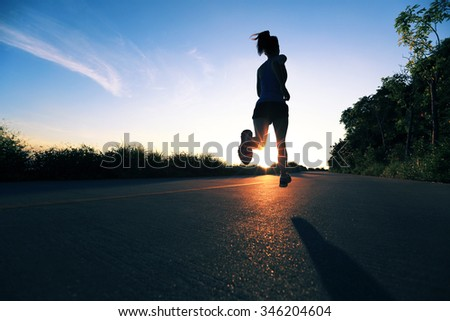 young fitness woman running on sunrise seaside trail - stock photo
