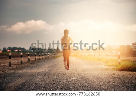 young fitness woman running on the road in the morning.