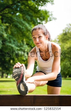 Young fitness woman stretching muscles before sport activity - outdoor in park - stock photo