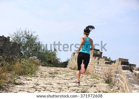 young fitness woman trail runner running at chinese great wall . woman fitness jogging workout wellness concept. - stock photo