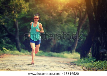 young fitness woman trail runner running in forest - stock photo