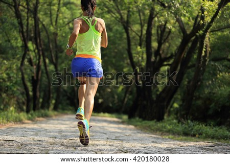 young fitness woman trail runner running on forest
