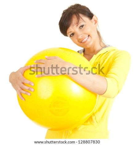 young fitness woman with big yellow ball, white background - stock photo
