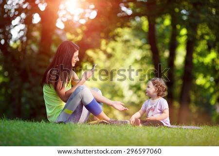 Young fitness woman with child doing exercises outdoors. Fitness training outdoors. Fitness classes outdoors. Attractive fitness woman. Workout outdoors. Healthy lifestyle. Fitness child - stock photo