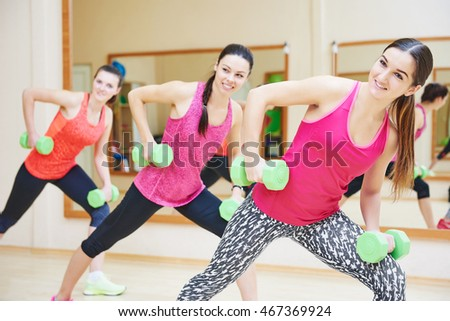 young fitness woman with dumbbell in gym