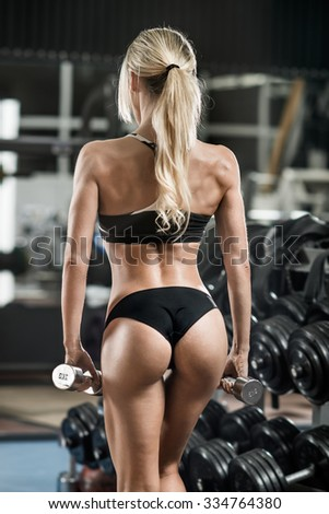 young fitness woman with dumbbells in gym, body back, vertical photo - stock photo