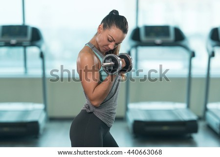 Young Fitness Woman Working Out Biceps In Fitness Center - Dumbbell Concentration Curls - stock photo