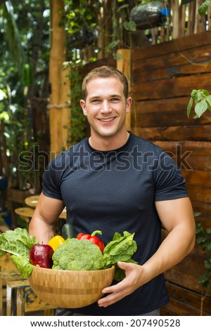 Young fitted man holding a bowl of organic vegetables from his kitchen garden.