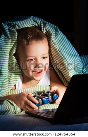 Young five years old boy hiding from mom under blanket playing computer games - stock photo