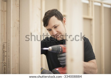 young fixer doing plasterboard partitioning  - stock photo