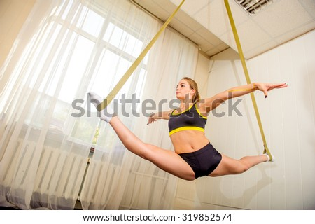 Young flexible attractive gymnast girl posing in the gym - stock photo