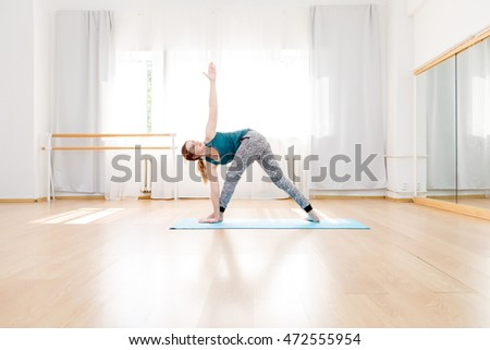 Young flexible blonde woman in utthita trikonasana triangle pose indoor