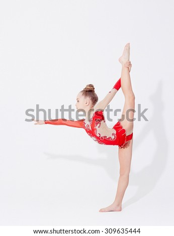 Young flexible girl in red dress doing gymnastic exercises. - stock photo